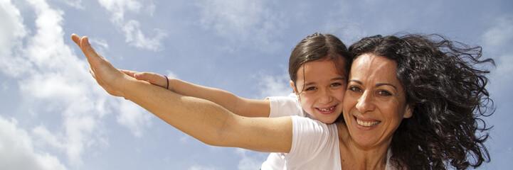Madre e hija sonriendo y volando con el cielo de fondo