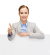 smiling businesswoman with white blank board