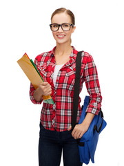 female student in eyeglasses with bag and folders