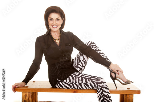 older woman zebra pants sit on bench smiling