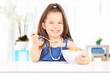 Cute little girl eating cereal from bowl seated on table
