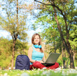Female student with headphones working on a laptop in park