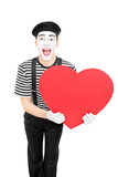 Male mime artist holding a big red heart