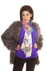 woman purple shirt fur coat hands hips