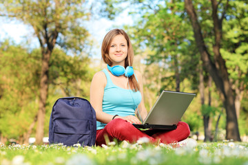 Female student with headphones relaxing in park