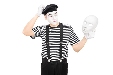 Male mime artist holding a theater mask