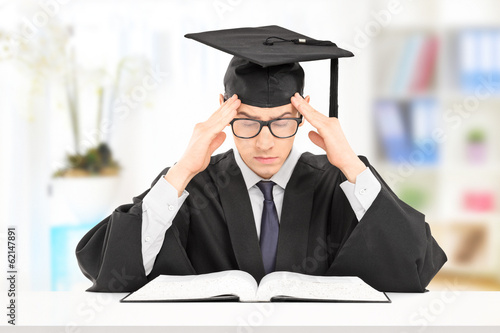 Male student in graduation gown studying indoors