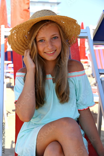 Beautiful girl in hat on beach
