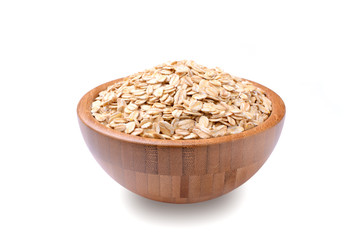 a bowl of uncooked rolled oats isolated on white background