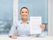 happy businesswoman holding contract in office
