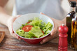 close of male hand holding a bowl with salad