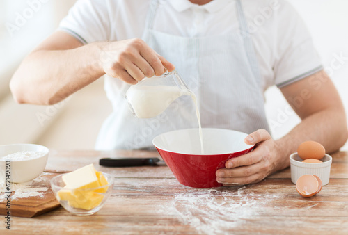 close up of male hand pouring milk in bowl