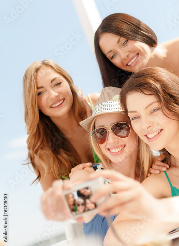 smiling girls taking photo in cafe on the beach