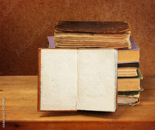 Books stack and opened book on wooden table