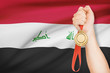 Medal in hand with flag on background - Republic of Iraq