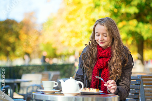 Girl eating waffles in a Parisian outdoor cafe