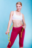 Fitness woman fit girl with measure tape measuring her waist