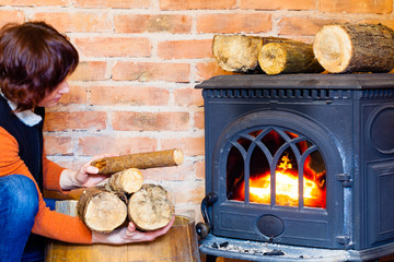 Woman putting some more wood on fireplace. Heating.