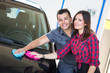 Young Couple Washing Car Together