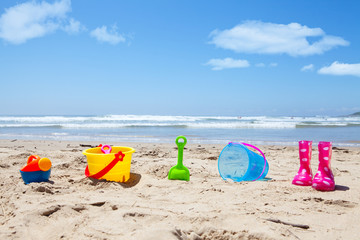 Colorful plastic toys and gumboots on beach sand