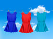 Set of colored dresses hanging on a clothesline on a sunny day.