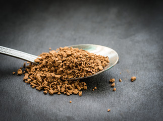 Instant coffee granules in metal spoon. Selective focus.