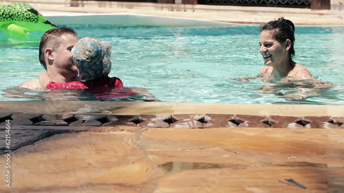 Happy family playing in hotel swimming pool
