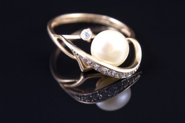 gold ring with a pearl is reflected from the floor