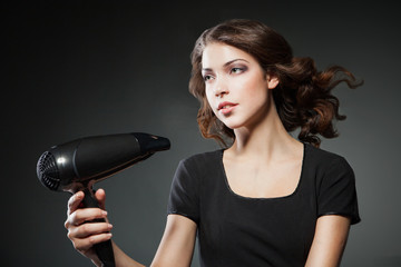 girl dries hair by hairdryer over dark background