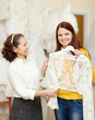 assistant  helps to girl chooses  bridal clothes