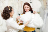 happy women chooses fur cape at wedding store