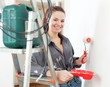 woman in grey shirt paints wall with roller