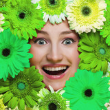 Happy smiling girl with flowers around her face. Green concept