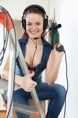 Portrait of happy girl in headphones with drill
