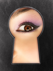 Female curiosity - woman eye looking through the keyhole