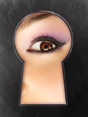 Female curiosity - woman eye looking through the keyhole