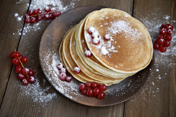 Pancakes with red currants and icing sugar