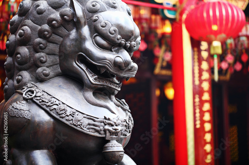 Lion statue in front of chinese temple Poster