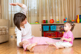 Mom and kid doing exercises sitting on the floor in home interio