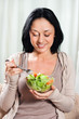 Young beautiful woman is eating salad