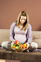 Pregnant woman sitting on sofa with bowl full of fruit