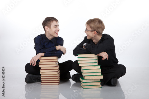 Two teenagers with piles of books on a white background
