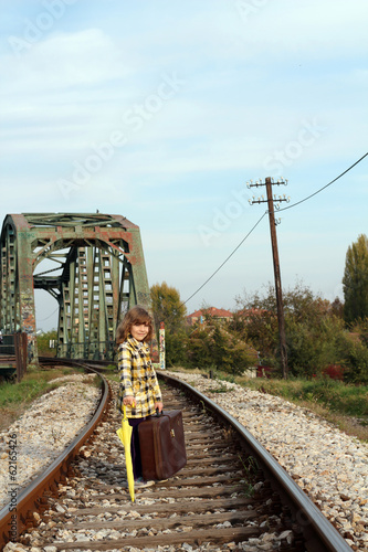 little girl with umbrella and suitcase on railroad