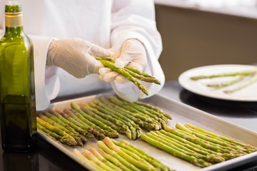 Hands with fresh asparagus and oil in kitchen