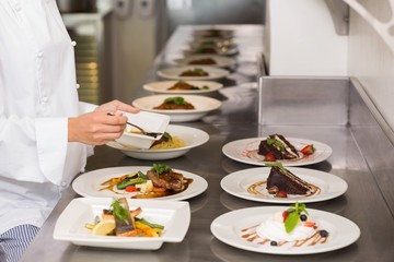 Mid section of a female chef garnishing food in kitchen