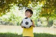 Happy cute little boy with football at park