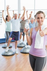 woman gesturing thumbs up with people stretching hands fitness