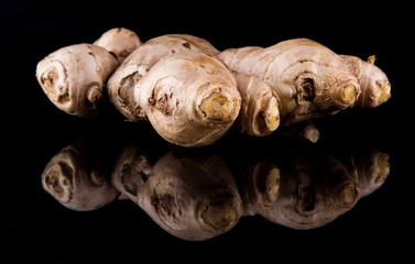 Fresh ginger root over black background