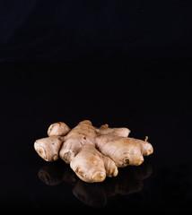 Fresh ginger root over black background