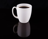 Coffee in a white mug over black background